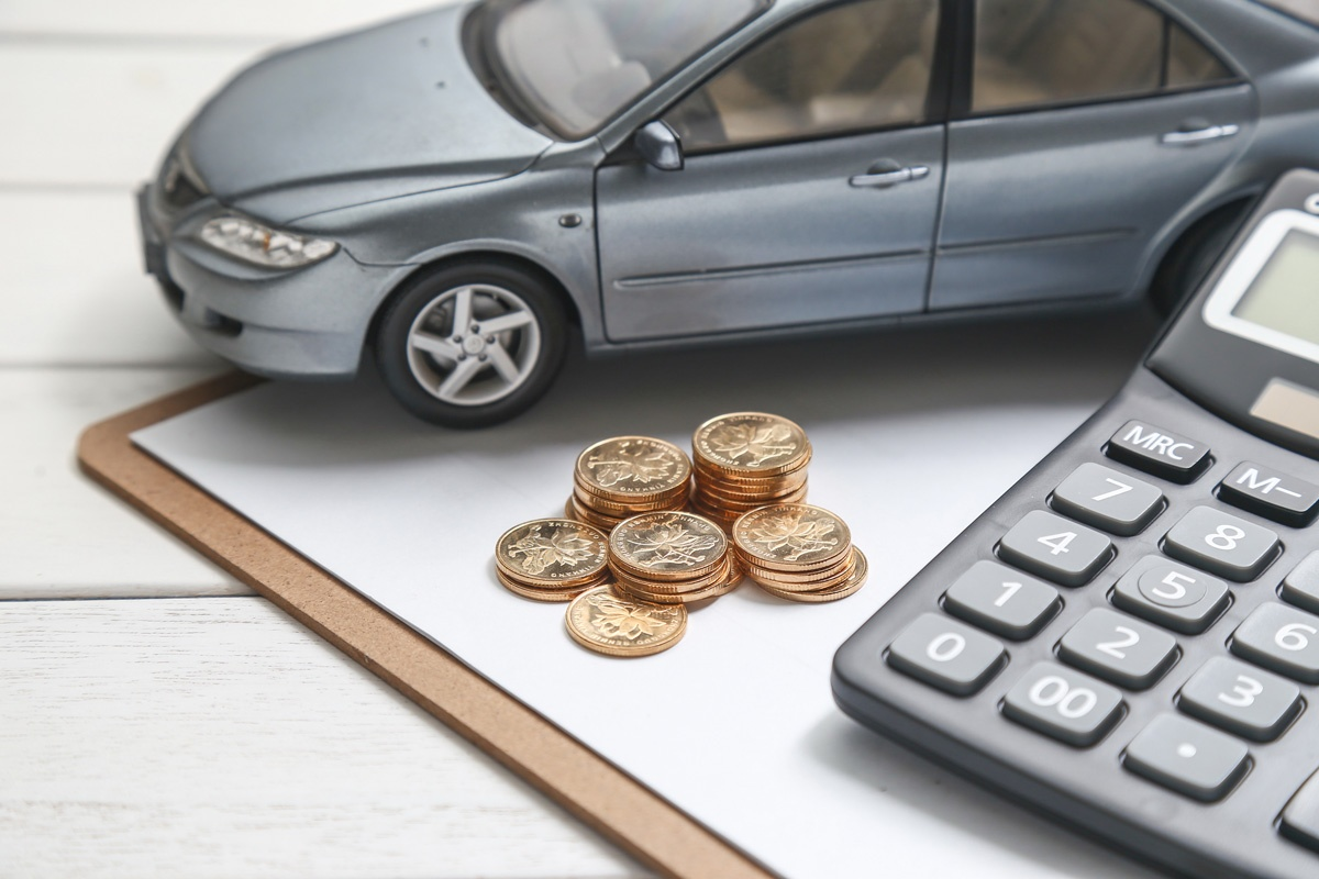 monety a obok miniatura auta i kalkulator